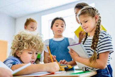 pupils writing off homework of their classmate during break