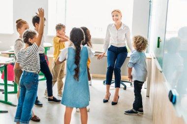 group of classmates standing around teacher at classroom and having fun