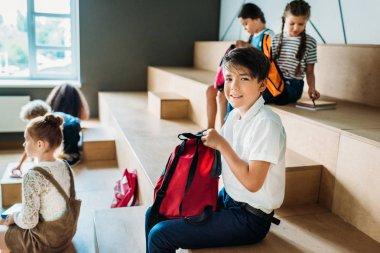group of schoolchildren with backpack sitting on wooden tribune at school corridor