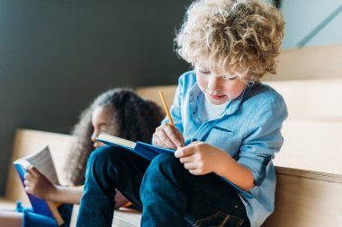concentrated multiethnic schoolchildren writing in notebooks together