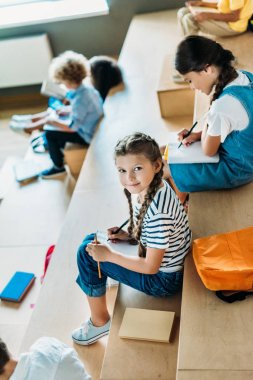 high angle view of schoolgirl with notebook studying on tribune at school corridor while her classmates sitting on background