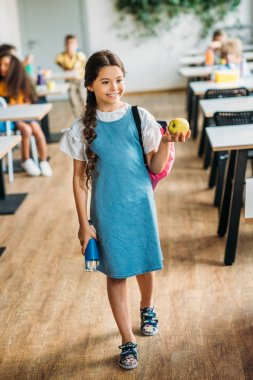 happy little schoolgirl with apple and bottle of water at school cafeteria