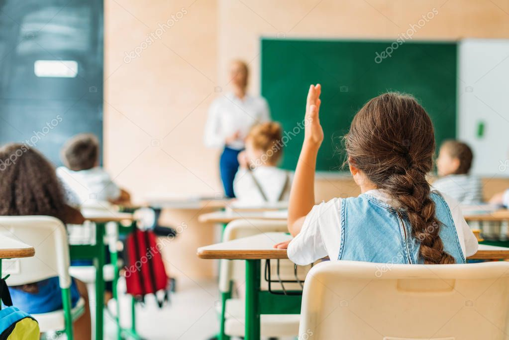 Back view of schoolgirl raising hand to answer teachers question during lesson stock vector
