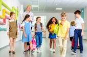 Gruppe glücklicher Klassenkameraden läuft durch den Schulflur