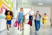 entzückend glückliche Schulkinder laufen gemeinsam mit dem Lehrer durch den Schulflur
