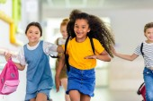 Fotografie adorable happy schoolchildren running by school corridor together
