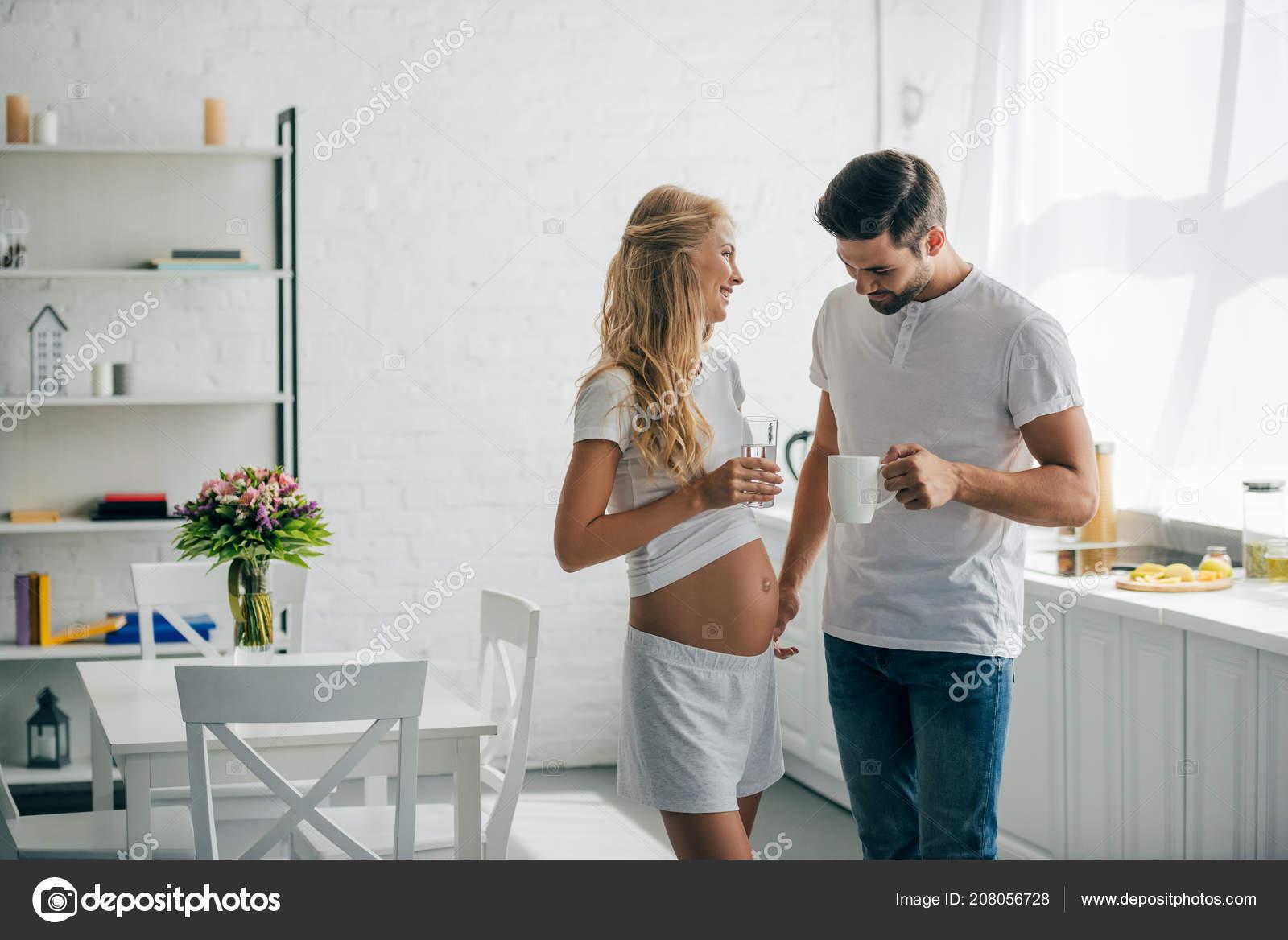 86bb089aa168 Человек с чашечкой кофе, глядя на живот беременной жены на кухне дома —  Фото автора ArturVerkhovetskiy