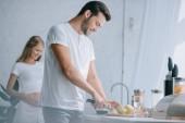Fotografie selektiven Fokus der Mann Schneiden von Früchten am Schalter mit schwangeren Frau hinter in die Küche zu Hause