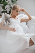 portrait of pregnant woman in white nightie with teddy bear resting on sofa at home