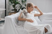 Fotografie smiling pregnant woman in white nightie with teddy bear resting on sofa at home