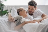 Fotografie pregnant woman in white nightie with teddy bear on sofa and husband near by at home