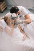 obscured view of man and pregnant wife in white nightie holding teddy bear on sofa at home