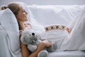 Fotografie side view of smiling pregnant woman in white nightie with teddy bear and wooden blocks with baby lettering on belly resting on sofa