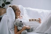 side view of smiling pregnant woman in white nightie with teddy bear and wooden blocks with baby lettering on belly resting on sofa