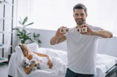 Fotografie selective focus of smiling man showing wooden blocks with baby inscription while pregnant woman resting on sofa