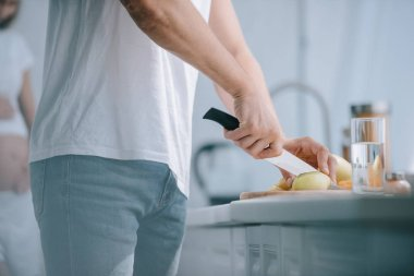 partial view of man cutting fruits at counter with pregnant wife behind in kitchen at home