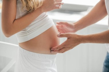 cropped shot of husband touching belly of pregnant wife at home