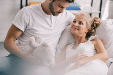portrait of man with teddy bear sitting near pregnant wife in white nightie on sofa at home