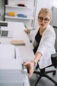 Fotografie mladá podnikatelka použití tiskárny v sedle na pracovišti s přenosným počítačem v kanceláři