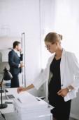 Fotografie Selektivní fokus těhotná podnikatelka pomocí tiskárny, zatímco kolega mluvit na telefonu v kanceláři