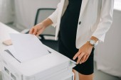 Fotografie partial view of pregnant businesswoman using printer in office