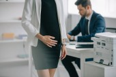 Fotografie partial view of pregnant businesswoman and colleague at workplace in office