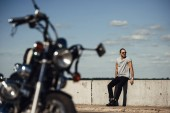 Fotografie selective focus of young biker with classic motorcycle on foreground