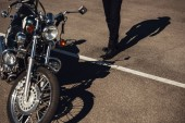Fotografie partial view of biker going to chopper motorcycle on road