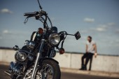 Fotografie selective focus of classical chopper motorbike and man on background