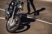 Fotografie cropped view of male biker going near classical chopper motorbike