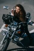 Fotografie curly woman sitting on chopper motorbike with helmet on urban parking