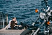 fiatal pár használ laptop ülve, a rakparton repülőtér közelében, a tenger, a szelektív összpontosít motorkerékpár