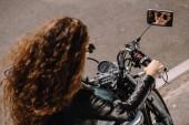 Fotografie krásná kudrnatá dívka sedí na motorce na parkování