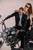 Fotografie two bikers sitting on classical cruiser motorcycle on asphalt road