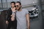 Muž, mluvil na smartphone zároveň dívka stojící na pozadí s motorky
