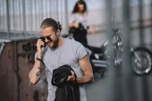 Muž, mluvil na smartphone zároveň dívka stojící s klasickou motorku
