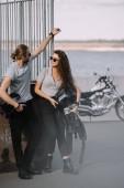 Fotografie pár motorkářů držení helmy, klasický chopper motocyklu na pozadí