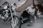Přítelkyně a přítel sedí na asfaltu s klasické chopper motocyklu