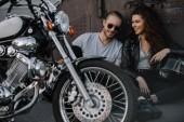 pár motorkářů sedí na asfaltu s chopper motocyklu