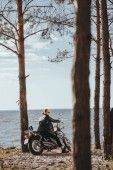 Fotografie biker in black leather jacket sitting on classic motorcycle near the sea in forest