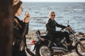 selective focus of man sitting on motorcycle while his girlfriend smoking on foreground