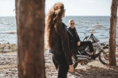 Fotografie selective focus of woman looking at biker sitting on classical motorcycle on seashore