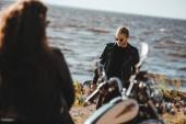 Selektivní fokus ženy sedí na motorce a při pohledu na přítele na pobřeží