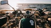 Camera point of view of biker sitting on classic motorbike on seashore
