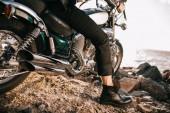 Fotografie nízké část pohled biker, sedí na klasické motorce