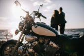 selective focus of classical chopper motorbike and couple looking at sea on background