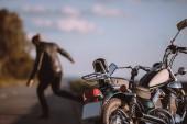 nefunkční klasický motocykl na silnici s rozzlobený motorkář na pozadí, Selektivní ostření