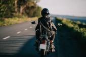 zadní pohled na páru v přilbách, jízda na motocyklu chopper na venkovské silnici
