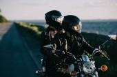 pár motorkářů v přilbách jízda klasického motocyklu na venkovské silnici