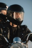 Fotografie two bikers in moto helmets sitting on motorcycle